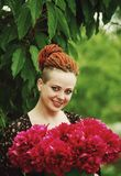 Beautiful young woman with peony flowers stock photo