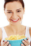 Beautiful young woman holding a bowl with raw pasta. Royalty Free Stock Photography