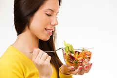 Beautiful young woman, holding bowl of salad and smiling Stock Photo
