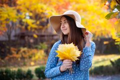 Beautiful young woman holding a bunch of autumn leaves. Gorgeous young woman in autumn in park with big yellow leaves, smiling and enjoying nature. Natural stock photography