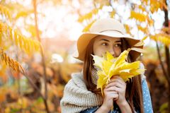 Beautiful young woman holding a bunch of autumn leaves. Gorgeous young woman in autumn in park with big yellow leaves, smiling and enjoying nature. Natural royalty free stock photos