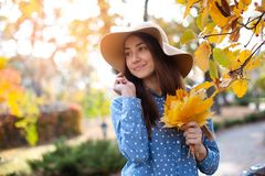 Beautiful young woman holding a bunch of autumn leaves. Gorgeous young woman in autumn in park with big yellow leaves, smiling and enjoying nature. Natural stock image