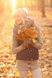 Beautiful young woman holding a bunch of autumn leaves Stock Images