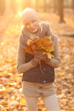 Beautiful young woman holding a bunch of autumn leaves. Young woman in autumn park royalty free stock image