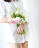 Beautiful young woman holding a bunch of delicate spring pink tu Royalty Free Stock Photography