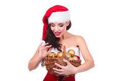 Beautiful young woman holding Christmas balls in basket isolated. Xmas and New Year preparation Royalty Free Stock Image