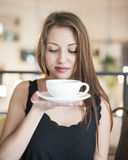 Beautiful young woman holding coffee cup and saucer at cafe Royalty Free Stock Photography
