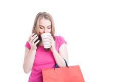 Beautiful young woman holding coffee cup and shopping bags Royalty Free Stock Image