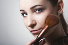 Beautiful young woman holding different make-up brushes. Stock Images