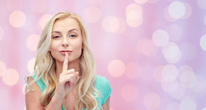 Beautiful young woman holding finger at her lips Royalty Free Stock Photo