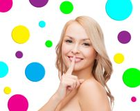 Beautiful young woman holding finger on lips Stock Photos