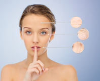 Beautiful young woman holding finger on lips Royalty Free Stock Images