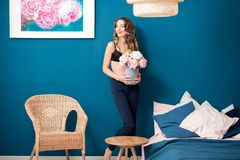 Woman with flowers at home. Beautiful young woman holding flowers standing in the cozy bedroom on the blue wall background at home royalty free stock photo
