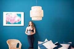 Woman with flowers at home. Beautiful young woman holding flowers standing in the cozy bedroom on the blue wall background at home royalty free stock photos