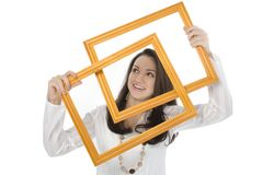 Beautiful Young Woman Holding Frames in Front of Face Stock Photo