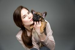 Girl with french bulldog puppy. Beautiful young woman holding french bulldog puppy dog. happy expression. copy space Stock Images