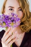Beautiful young woman holding fresh purple flowers and looking at camera. Isolated on grey royalty free stock images