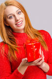 Beautiful young woman holding in front a Christmas present. Stock Photo