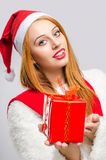 Beautiful young woman holding in front a Christmas present. Royalty Free Stock Photos