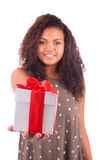 Beautiful young woman holding a gift over a white background. Royalty Free Stock Photos