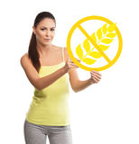 Beautiful, young woman holding a gluten free symbol. Over white background Royalty Free Stock Image