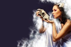 A beautiful young woman holding a goat skull Stock Image