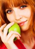 Beautiful young woman holding a green apple royalty free stock image