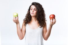 Beautiful young woman holding green and red apples over white background. Portrait of beautiful young woman holding green and red apples over white background stock images