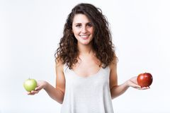 Beautiful young woman holding green and red apples over white background. Portrait of beautiful young woman holding green and red apples over white background stock photos