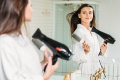 Beautiful young woman holding hair brush and drying hair at mirror. In bathroom royalty free stock photos