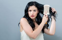 Beautiful young woman holding a hairbrush. On a gray background stock image