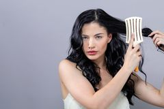 Beautiful young woman holding a hairbrush. On a gray background royalty free stock photo