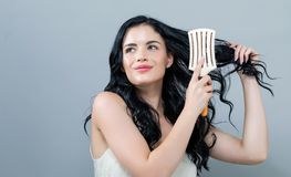 Beautiful young woman holding a hairbrush. On a gray background stock photography