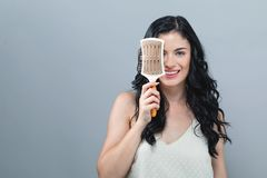 Beautiful young woman holding a hairbrush. On a gray background royalty free stock photos