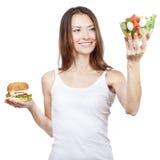 Beautiful young woman holding hamburger and salad Royalty Free Stock Photography