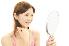 Beautiful young woman holding a hand mirror Stock Photos