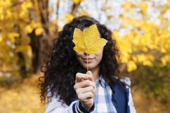 Girl closed face with maple leaf in hand stock photo