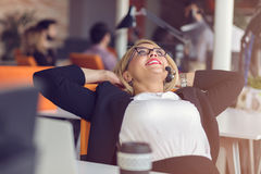 Beautiful young woman holding hands behind head and smiling while sitting at her working place in office Stock Photos