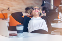 Beautiful young woman holding hands behind head and smiling while sitting at her working place in office Stock Photo