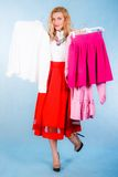 Beautiful young woman holding a heaps of clothes Royalty Free Stock Image