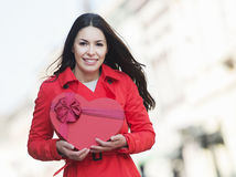 Beautiful young woman holding a heart shaped present Stock Images