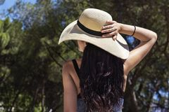 Beautiful young woman holding her hat with one hand Royalty Free Stock Images
