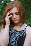 Beautiful young woman holding her head in her hands Royalty Free Stock Photo