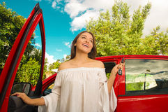 Beautiful young woman holding her keys and smiling near to her own red car Royalty Free Stock Photos