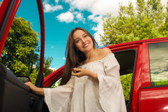 Beautiful young woman holding her keys and smiling near to her own red car Stock Photos