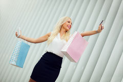 Beautiful young woman holding her shopping bags up high. Royalty Free Stock Images