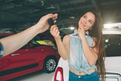 Beautiful young woman is holding a key in car dealership. Auto business, car sale, - happy female model in auto show or. Beautiful young women is holding a key Stock Photography
