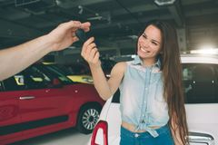 Beautiful young woman is holding a key in car dealership. Auto business, car sale, - happy female model in auto show or. Beautiful young women is holding a key Royalty Free Stock Images