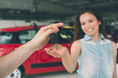 Beautiful young woman is holding a key in car dealership. Auto business, car sale, - happy female model in auto show or. Beautiful young women is holding a key Royalty Free Stock Photography