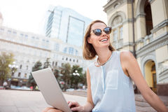 Beautiful young woman holding a laptop. Big city girl. Happy and content young woman holding laptop sitting on steps outdoors stock image